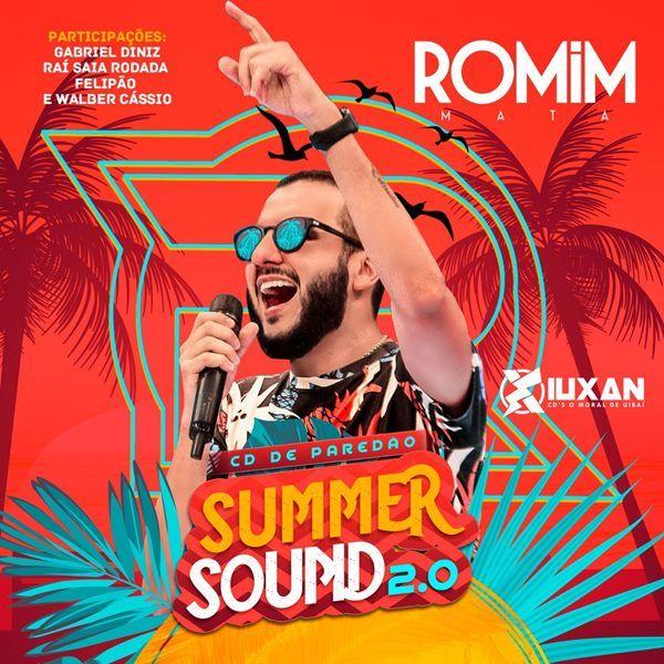 De óculos escuros e barba, Romim Mata canta e ergue o braço esquerdo