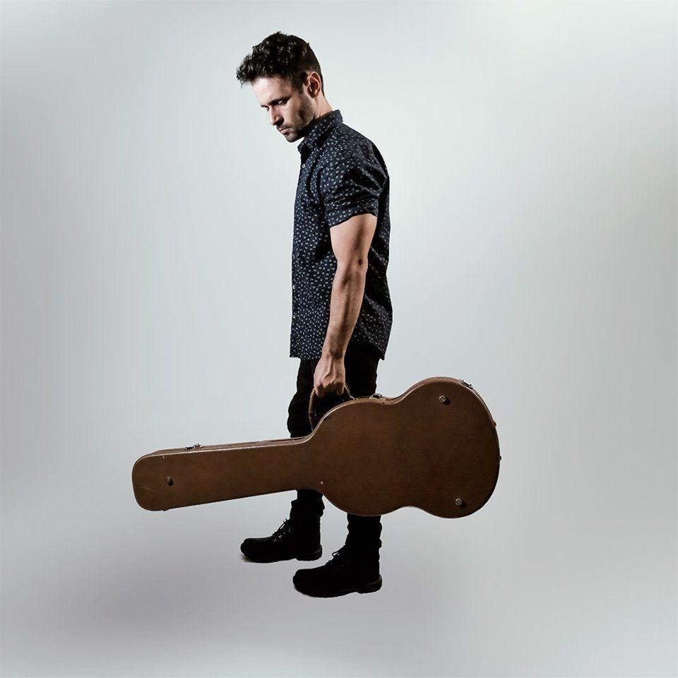 O músico Serginho Freitas segura o case de seu violão