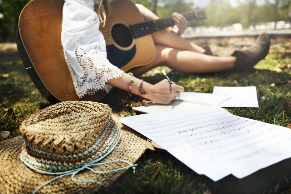 Com violao no colo, mulher escreve musica sentada na grama de um jardim