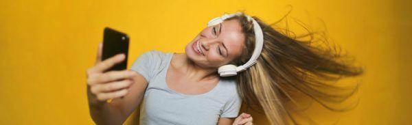 Mulher loira ouve músicas no fone de ouvido