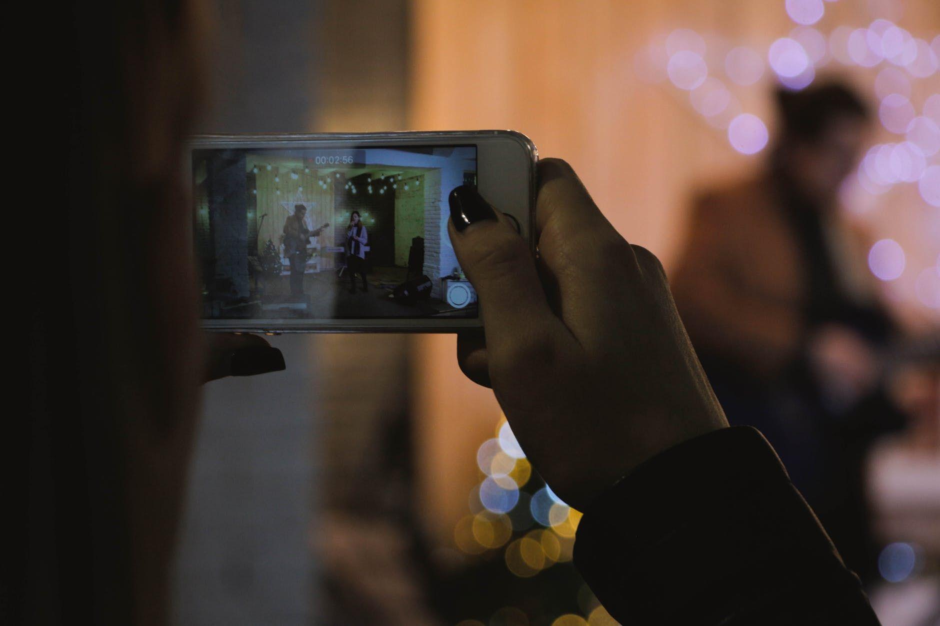 Mulher usa telefone celular para fazer foto profissional de uma banda
