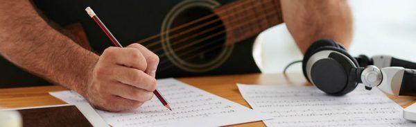 Compositor escreve partitura e mantém o violão no colo