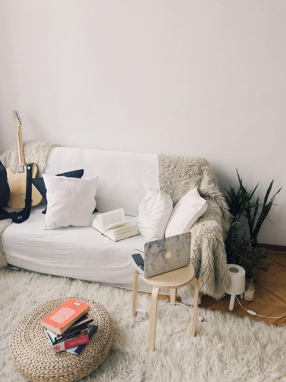 Sala de estar com sofá, guitarrae notebook