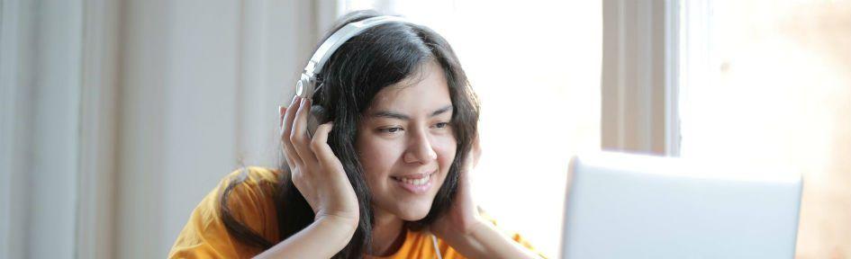 Garota com traços orientais ouve música no fone de ouvido