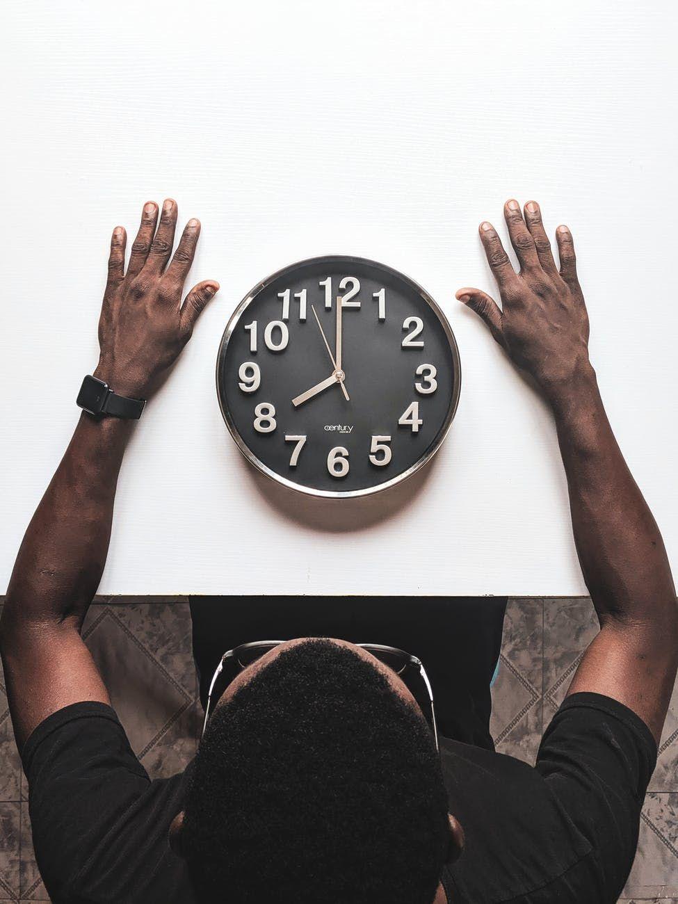 Homem sentado à mesa, observa um relógio de parede