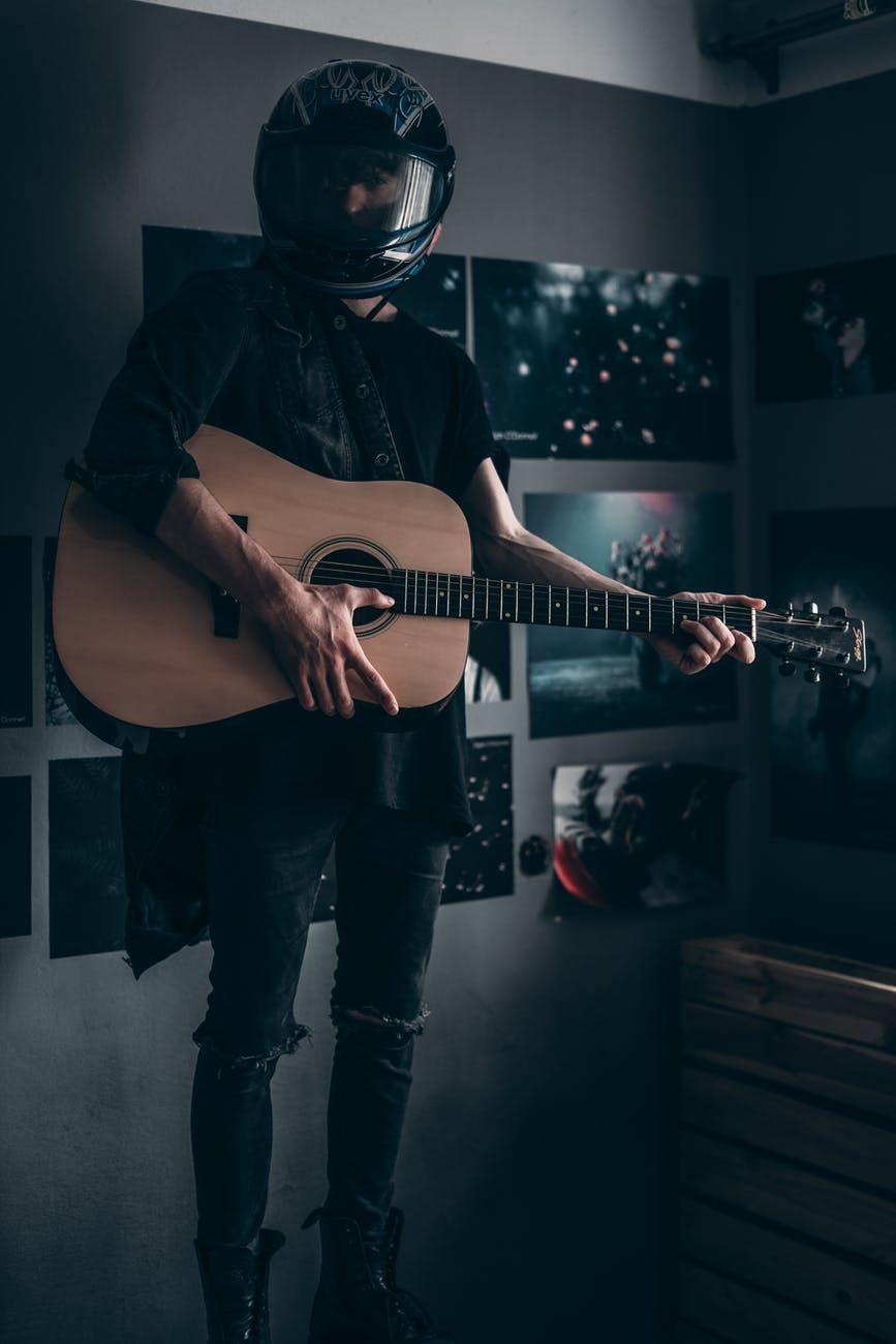 Jovem segura violão e usa capacete