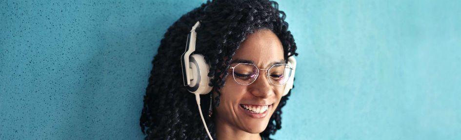 Garota negra, com fones de ouvido e sorridente