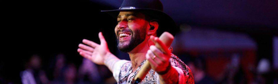 O Embaixador Gusttavo lima usandp chapéu de cowboy e cantando ao vivo