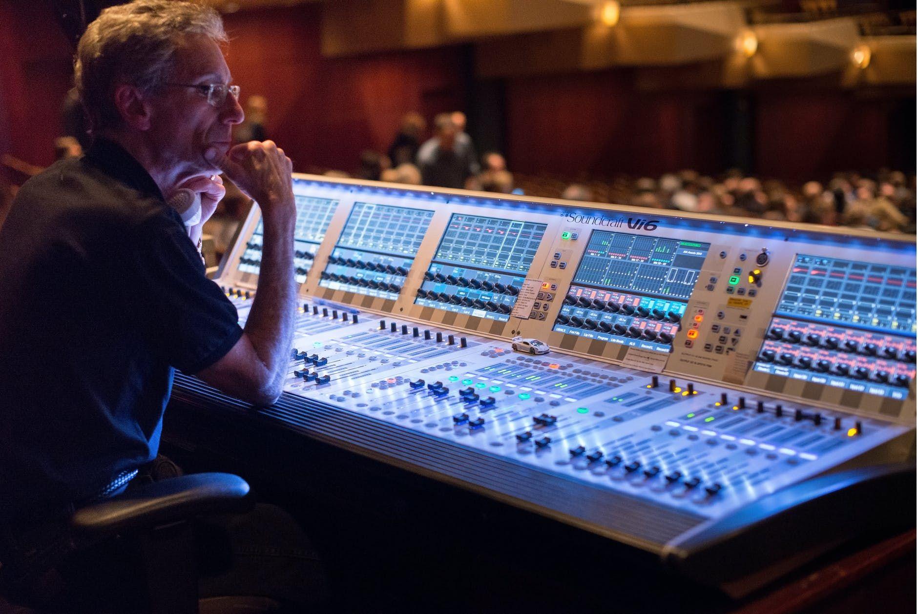 Técnico de áudio diante de uma mderna mesa de som, controlando a sonorização de um teatro