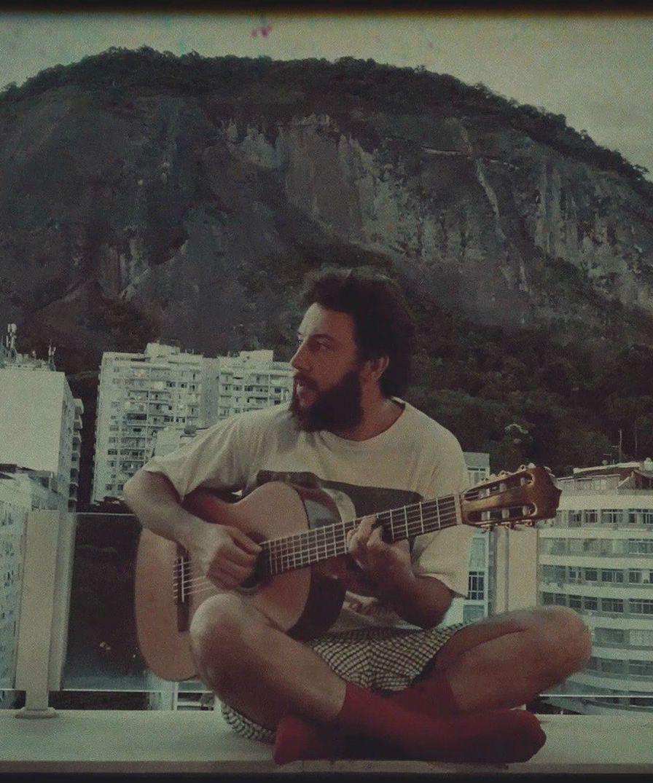 Pedro Mann na sacada de sua casa, no rio de janeiro, tocando violão
