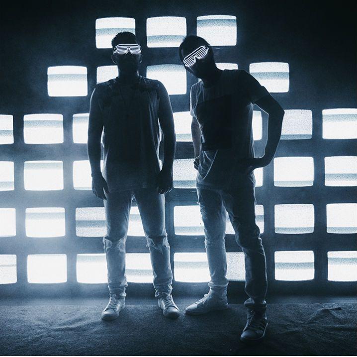 INtegrantes do duo gallena em frente a aparelhos de televisão
