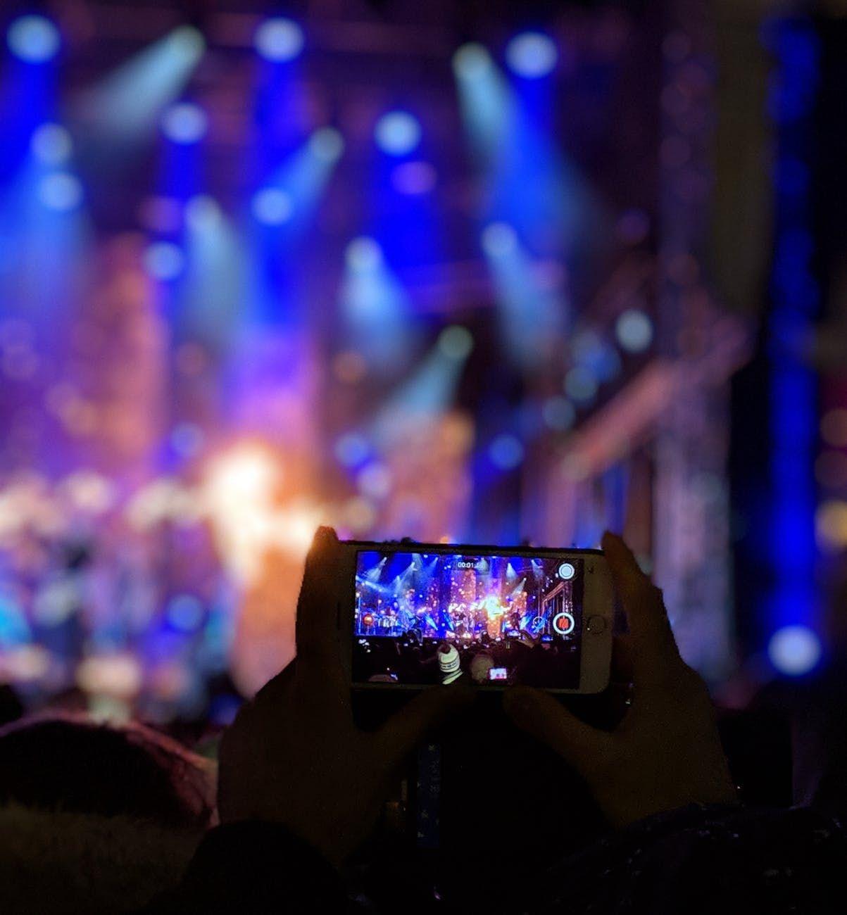 Fã usa telefone celular para grava vídeo em show