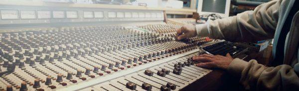 Produtor musical trabalha na mesa de som em estúdio