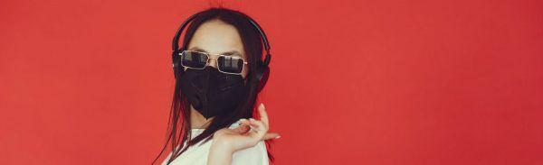Mulher usa máscara de proteção contra coronavírus, óculos escuros e fones de ouvido