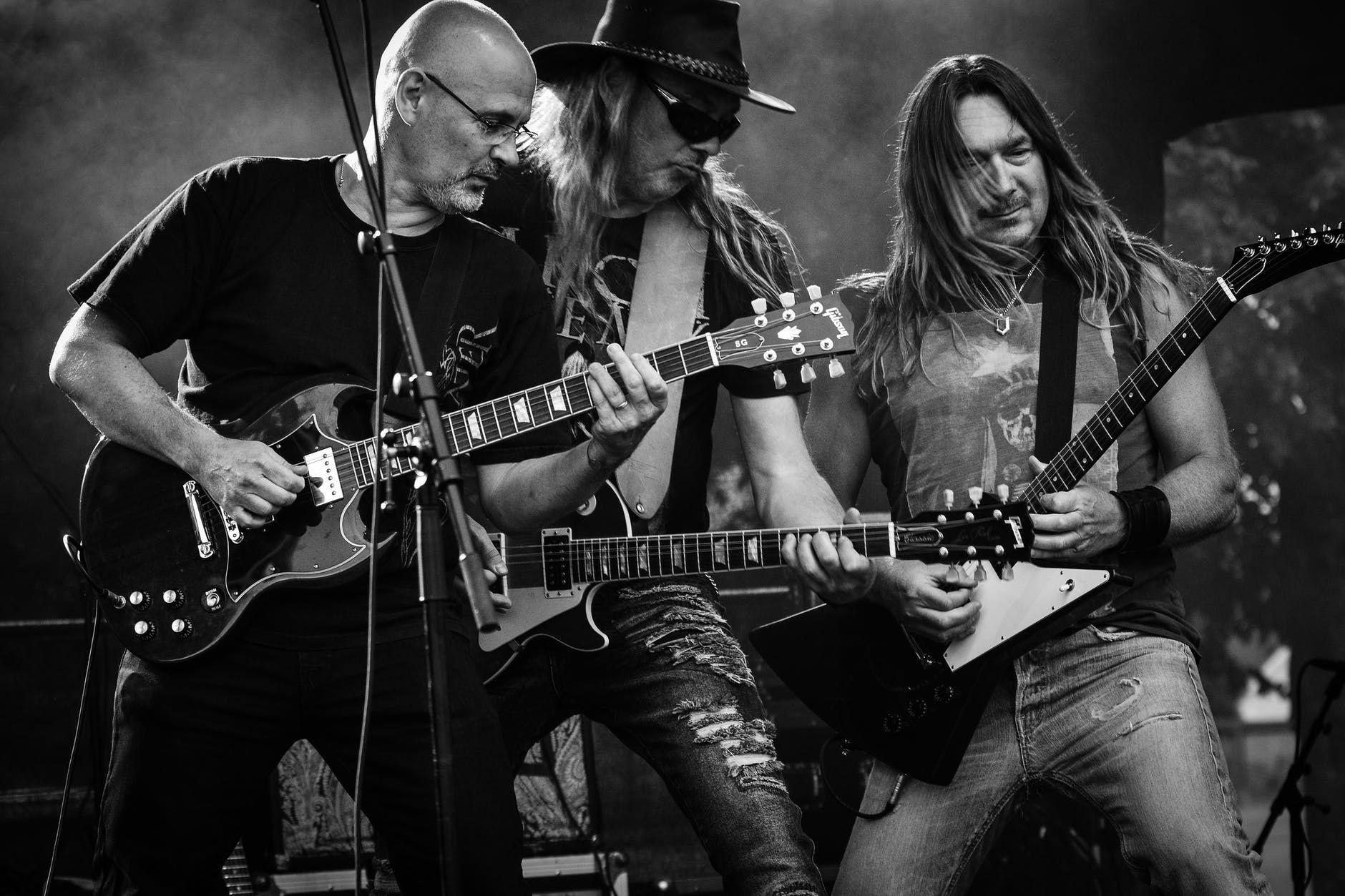 Três guitarristas de uma banda de rock fazendo um som ao vivo