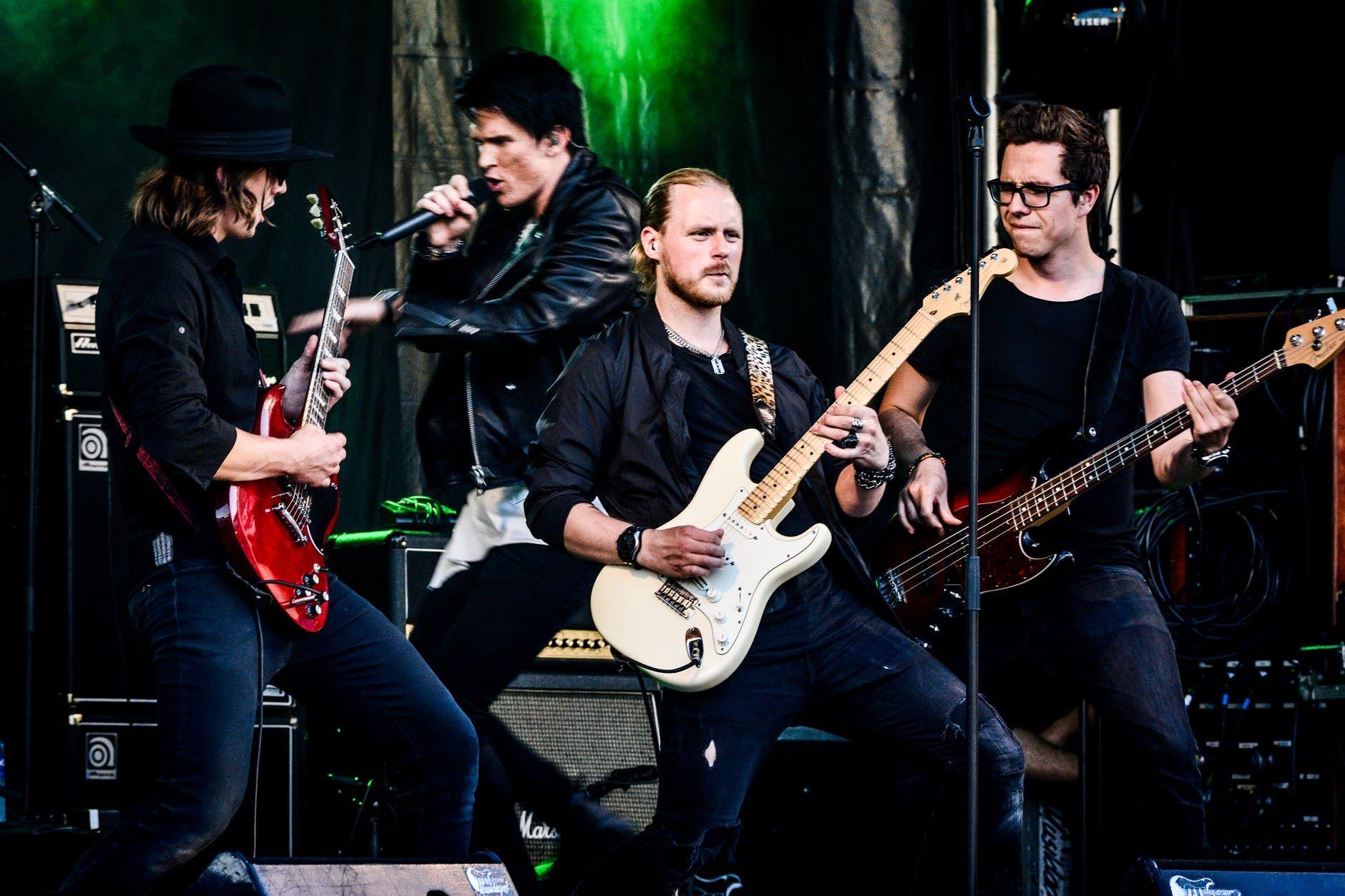 Membros de uma banda de rock tocando ao vivo