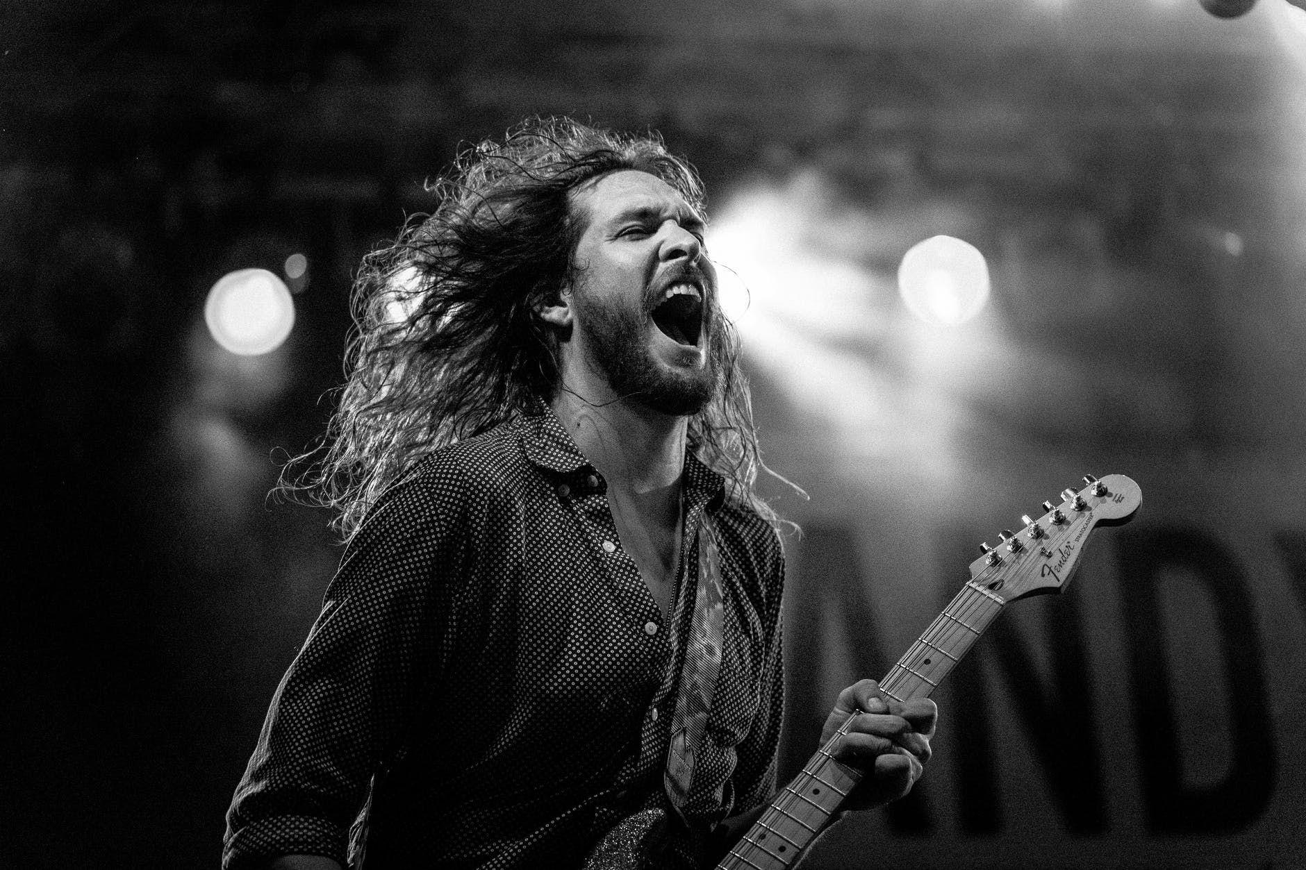 Guitarrista de cabelo grande faz solo de rock