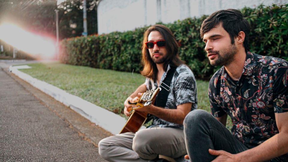 Membros da banda Verdecaffé sentados na calçada e tocando violão