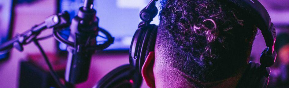 Com um par de fones nos ouvidos, Jovem negro grava voz em um home studio