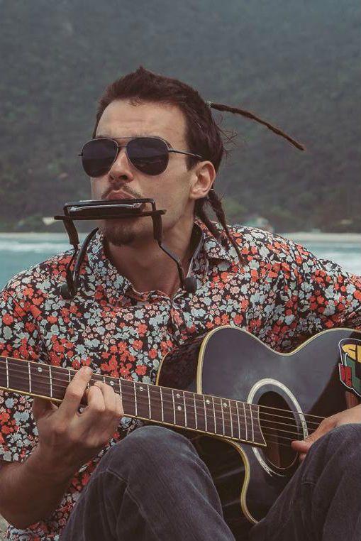 De costas para o mar, Lucas Plant toca violão e gaita