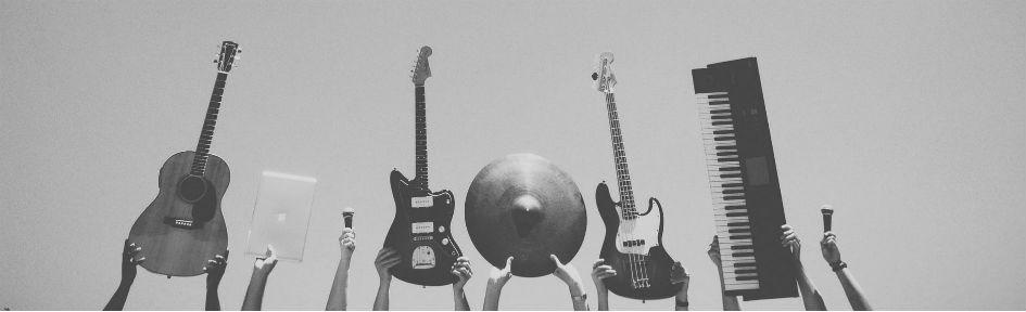 Instrumenos musicais em primeiro plano, as mãos dos músicos aparecem segurando