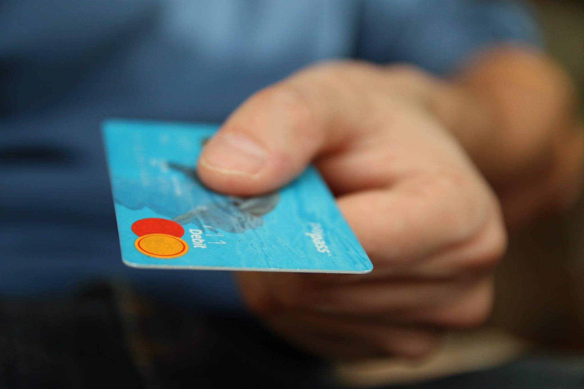 Mão de um homem oferece Cartão de débito como forma de pagamento