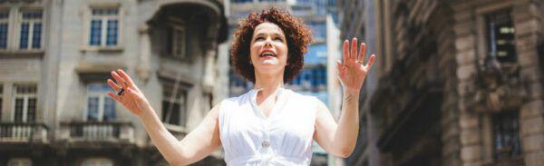 A cantora Glaucia Nasser, de vestido branco e braços abertos