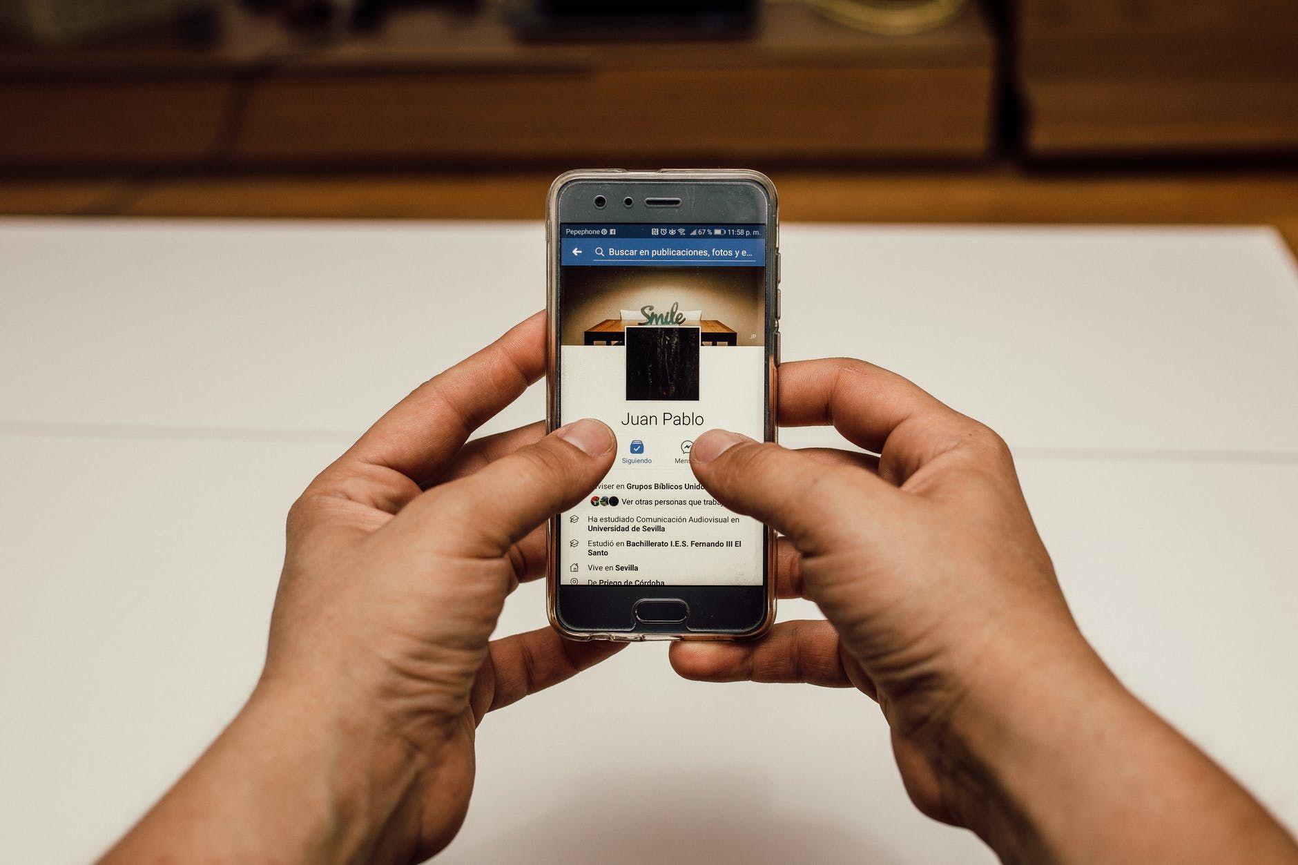 Usuário do Facebook observa seu perfil na tela de um smartphone