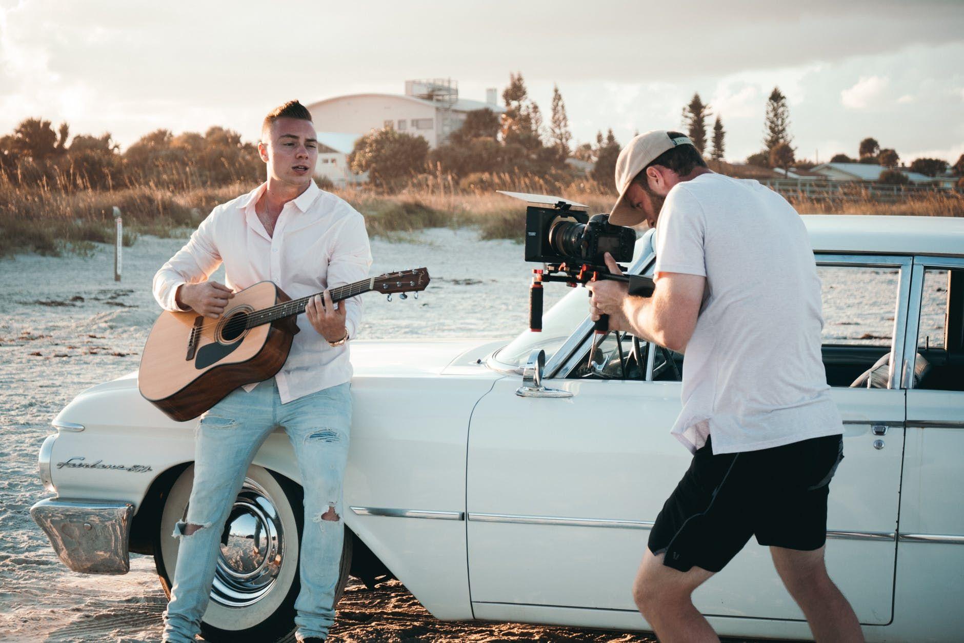 Músico sendo filmado, na praia, enquanto toca violão
