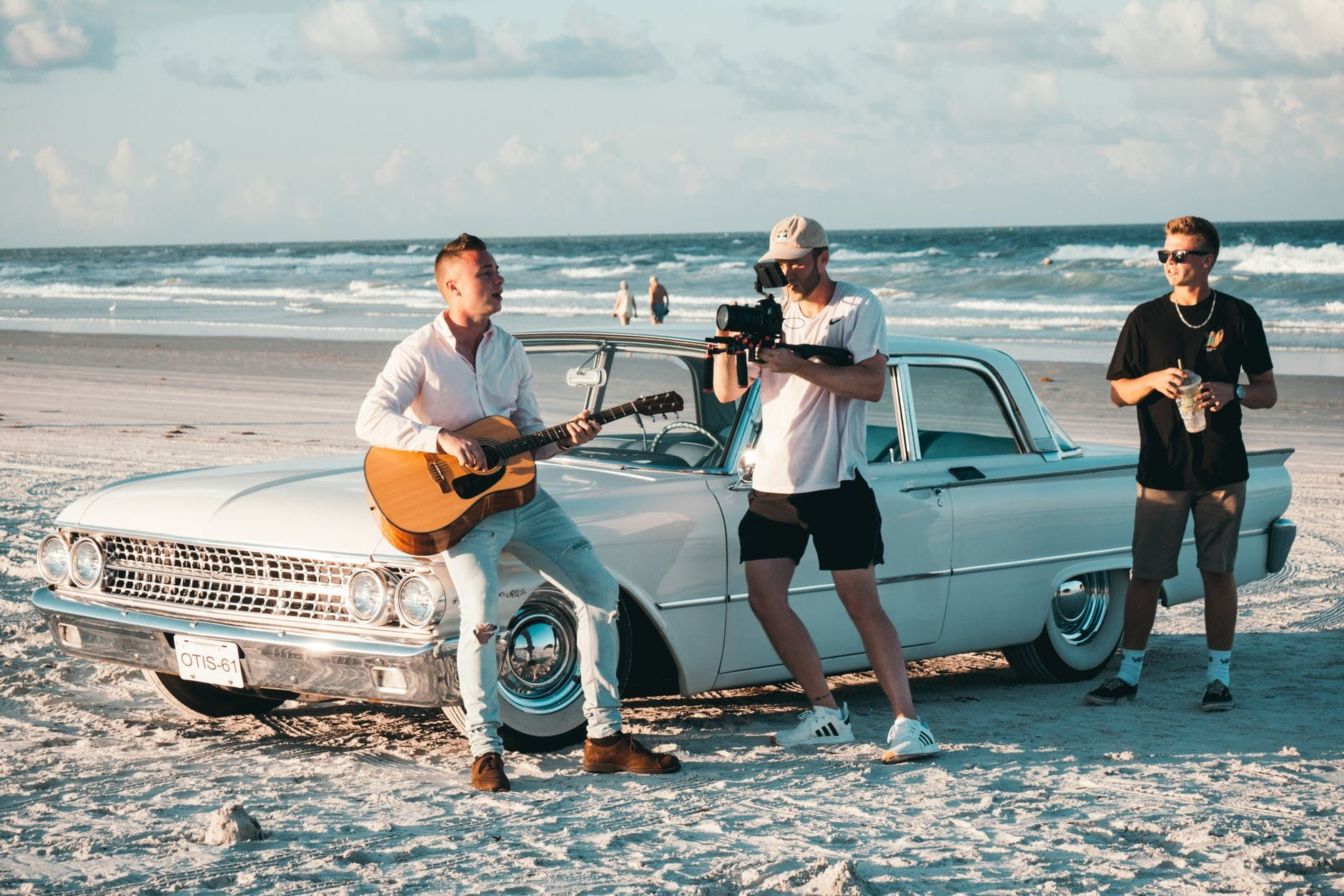 Músico grava vídeo tocando violão na praia