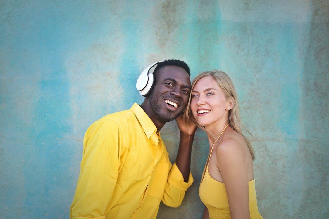Homem negro e mulher loira ouvindo música, juntos