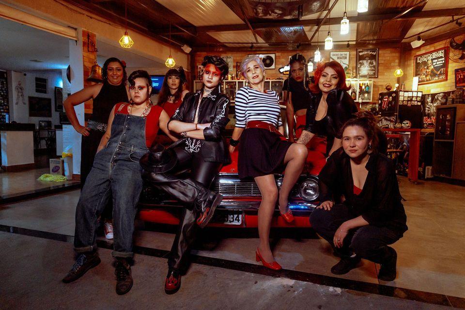 Integrantes da banda Ablusadas, mulheres brasileiras que tocam blues, posam de frente para um carro vermelho