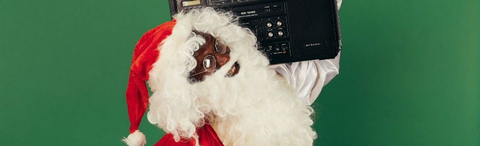 Papai Noel curtindo música em um sistema de som típico dos anos 80