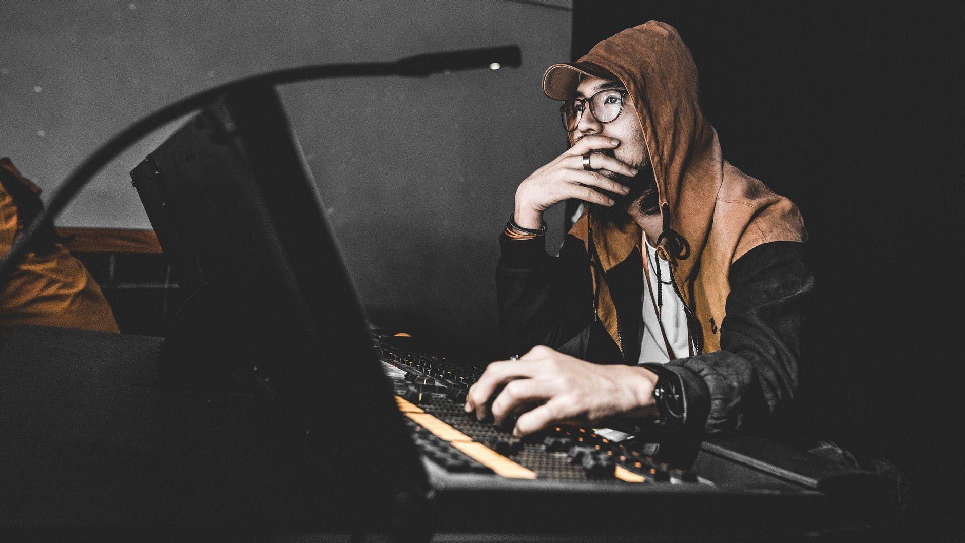 Técnico de áudio opera mesa de som durante gravação