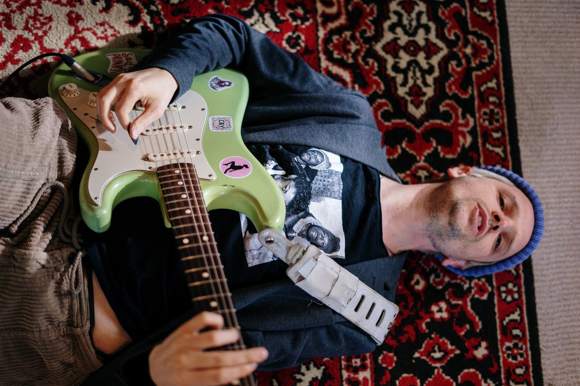 Guitarrista deita no chão durante gravação