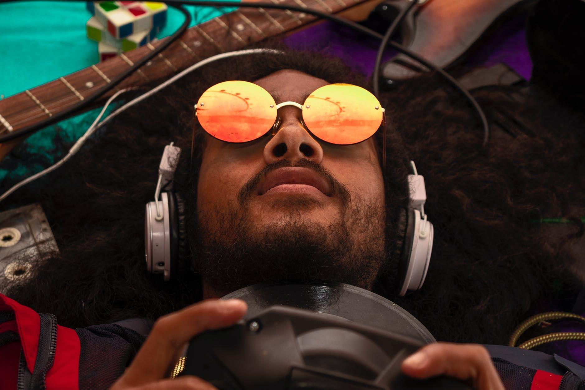 Homem negro jogando videogame e rodeado por instrumentos musicais