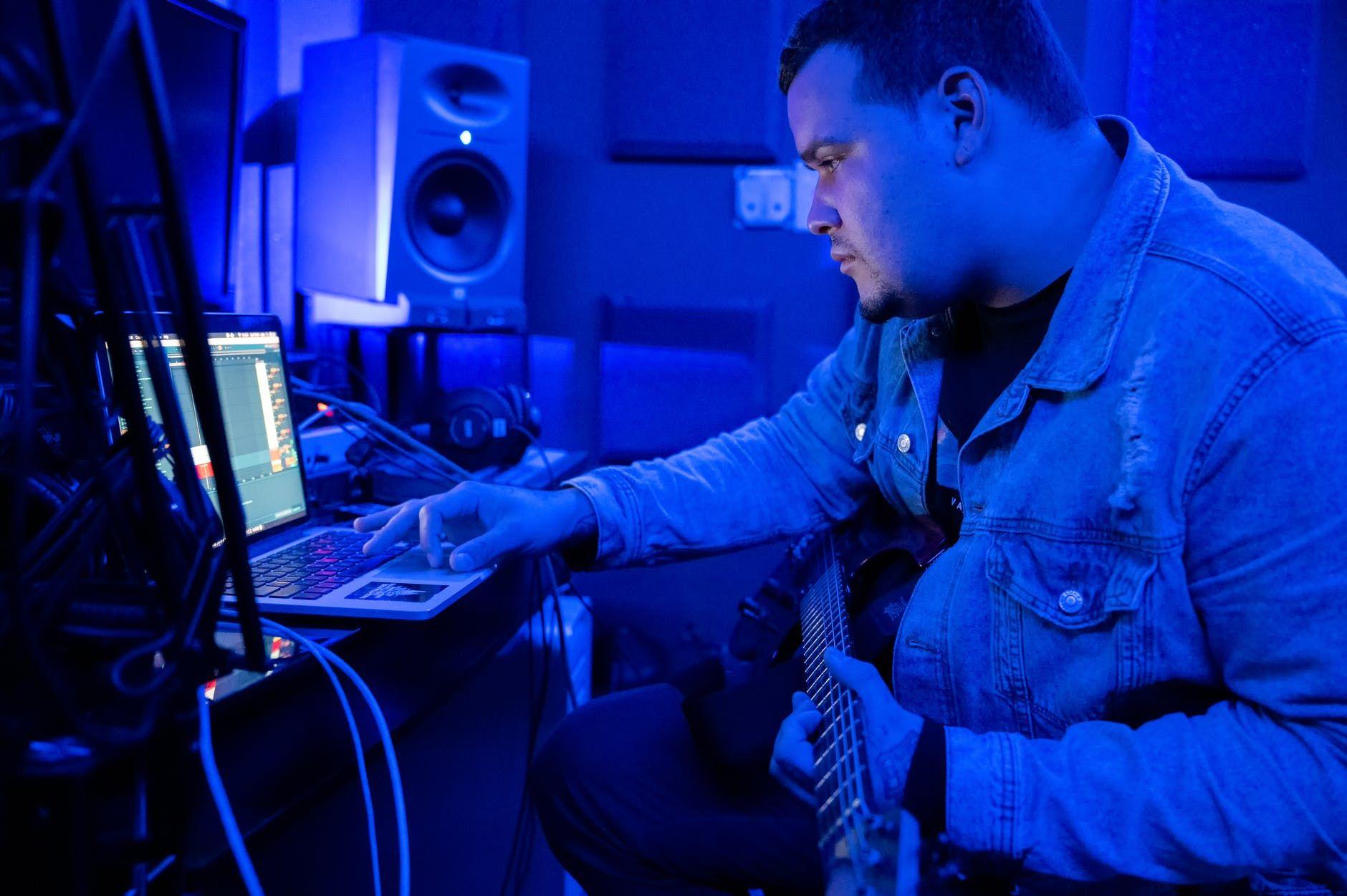 Guitarrista grava trilhas no computador, em home studio
