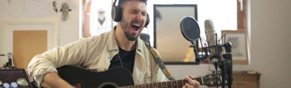 Músico grava voz e violão em estúdio
